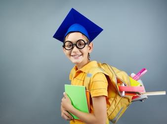 Colegial feliz con gafas negras y gorro de graduación