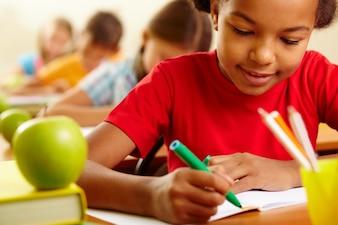 Colegiala concentrada con su lápiz verde