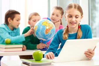 Colegiala inteligente con portátil en clase