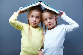 Colegialas jugando con un libro abierto