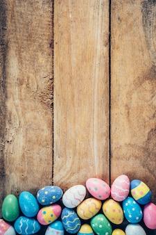 Coloridos huevos de pascua pastel sobre fondo de madera con espacio. Vintage entonado.