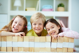 Compañeros de clase felices detrás de la construcción de madera