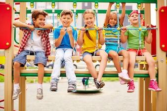 Compañeros de clase sonrientes sentados en fila en el parque infantil