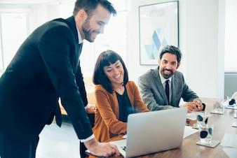 Compañeros de trabajo felices ríendo y usan un portátil