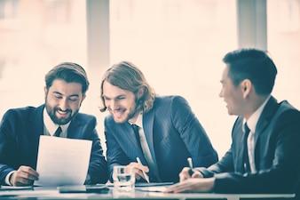 Compañeros de trabajo leyendo un documento y riendo
