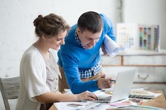 Compañeros de trabajo sonriendo mientras miran el portátil