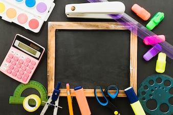 Composición con material escolar y pizarra