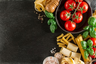 Composición con variedad de pasta, tomates y albahaca sobre superficie oscura