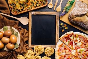 Composición de comida italiana con pizarra en medio