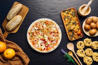 Composición de comida italiana con pizza en medio