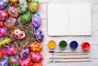 Composición de pascua con huevos, cuaderno y tarros de pintura