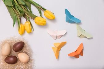 Composición de primavera con huevos de chocolate, tulipanes y mariposas de papel