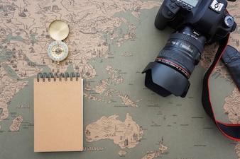 Composición de viaje con brújula, cámara y cuaderno