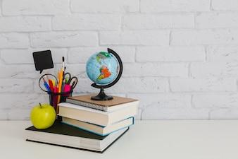 Composición escolar con libros, manzana y globo terráqueo