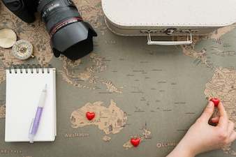 Composición fantástica con mano colocando corazones en el mapa