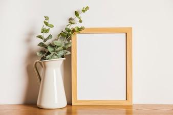 Composición floral con marco a lado de planta