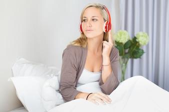 Concentrado, joven, mujer, escuchar, música, cama
