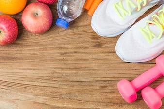 Concepto, botella de agua, mancuernas, zapatos deportivos, smartphone con auriculares y manzanas sobre fondo de madera. Espacio de la copia para el texto. Vista superior