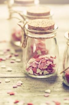 Concepto de amor con tarros en un fondo de madera, tonificación en colores pastel.