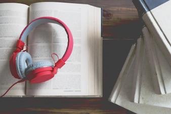 Concepto de audiolibro. Libros sobre la mesa con auriculares puestos en ellos.