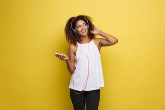 Concepto de estilo de vida - Retrato de hermosa mujer afroamericana alegre escuchar música en el teléfono móvil. Fondo amarillo pastel del estudio. Espacio De La Copia.
