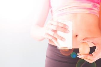 Concepto de estilo de vida saludable, la dieta y la aptitud, Fitness mujer celebración vaso de leche y huevo con copia espacio
