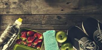 Concepto Del Deporte De La Vida Saludable. Zapatillas con manzanas, toallas y botellas de agua sobre fondo de madera. Espacio De La Copia.
