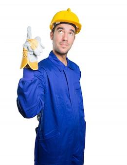 Confiado trabajador apuntando hacia arriba sobre fondo blanco