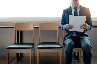 Confianza joven empresario sosteniendo el papel mientras está sentado en una fila de sillas, esperando la entrevista.