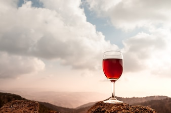 Copa de vino tinto y hermosa montaña de otoño