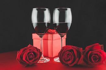Copas con vino tinto con un regalo y tres rosas