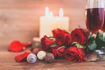 Copas de vino con velas encendidas y un ramo de rosas