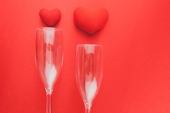 Copas de vino tumbadas en una mesa roja con corazones