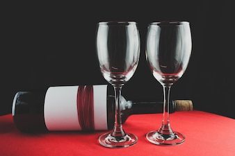 Copas de vino vacías con una botella al lado