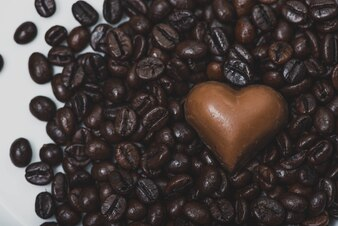 Corazón de chocolate sobre granos de café