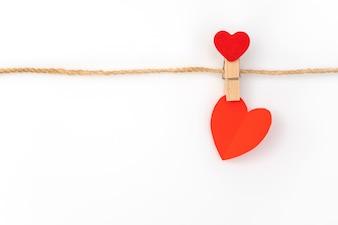 Corazón de papel rojo colgando en el fondo blanco.