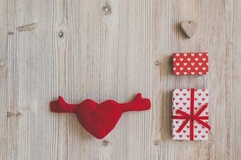 Corazón de peluche con brazos y manos y cajas de regalo
