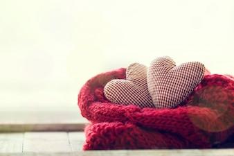 Corazones de peluche encima de una bufanda roja