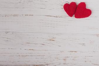 Corazones de tela rojos sobre una mesa de madera