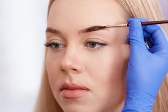 Cosmetologist que hace cejas permanentes usando cepillo.