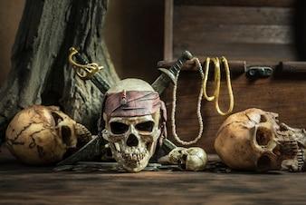 Cráneo del pirata con dos espadas y cofre del tesoro