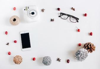 Creativo plano de la acción de gracias o el concepto de otoño con copia espacio en blanco, smartphone, cámara y lindos adornos sobre fondo blanco, vista superior