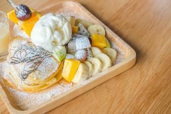 Crepe y las frutas con helado en la mesa.