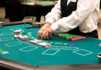 Crupier reparte cartas y fichas en una mesa de póquer