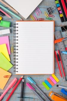 Cuaderno de papel y la escuela u oficina de herramientas en tabla de madera de época