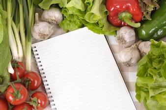 Cuaderno rodeado de verduras