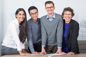 Cuatro hombres de negocios sonriente permanente en la mesa