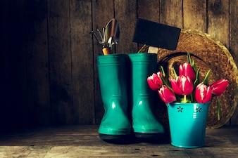 Cubo con flores rojas y botas de goma azules