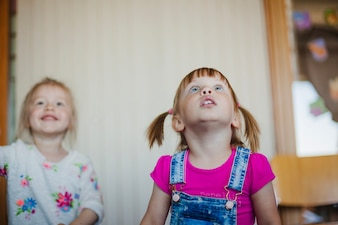 Cute niñas encantadoras mirando hacia arriba