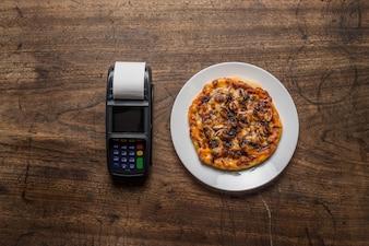 Deliciosas pizzas italianas servidas en mesa de madera con pago ter